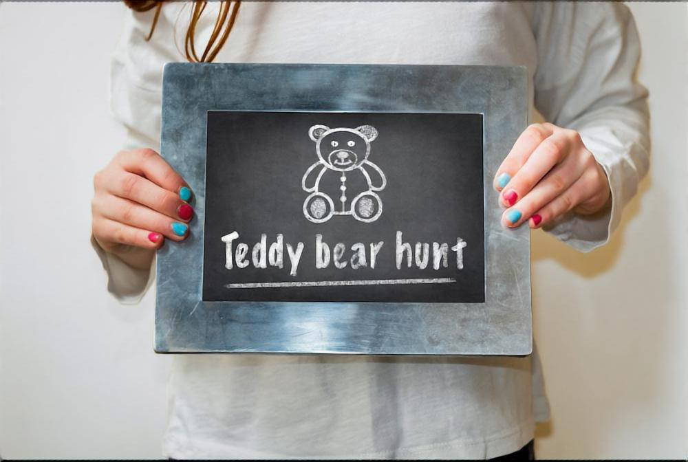 Girl holding a chalkboard with bear drawing and the text Teddy bear hunt. Teddy bear hunts keep children entertained during the corona virus lockdown.