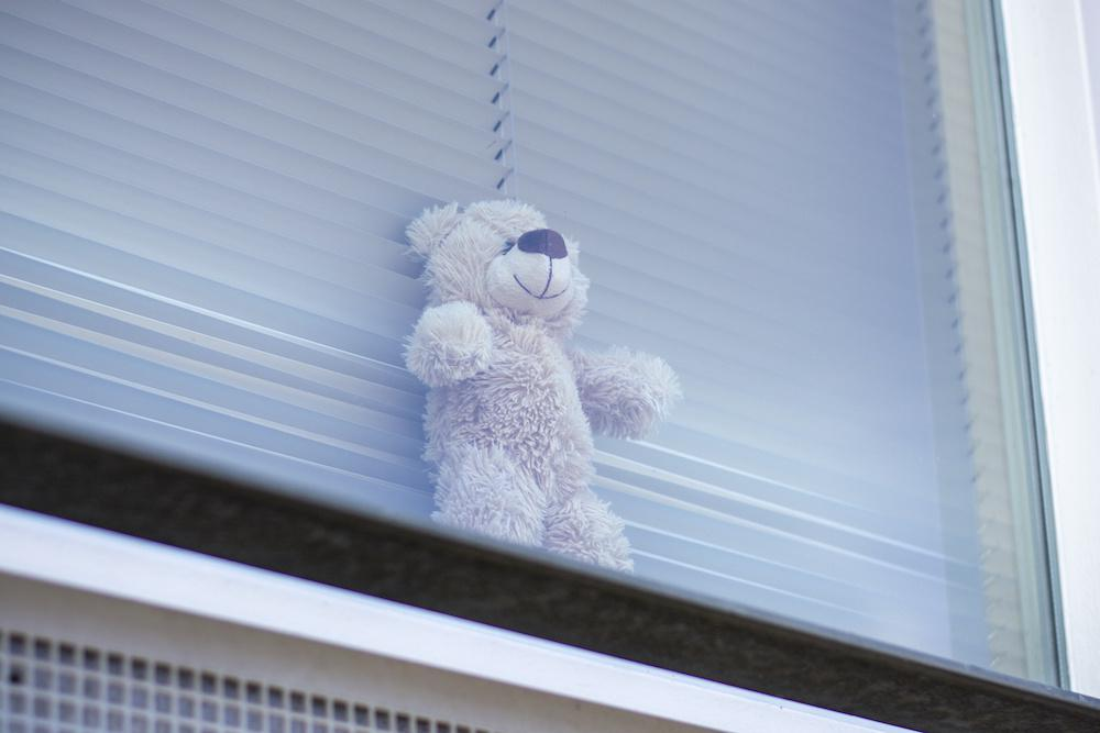 Teddy bear in window for children to 'bear hunt' during the coronavirus covid19 pandemic. Stuffed toys in windows to give children a fun and safe activity while walking around the neighbourhood during lockdown and social distancing